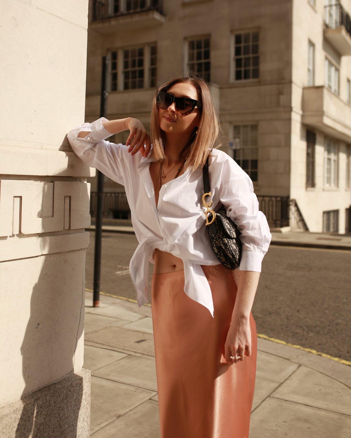 Lady wearing silk slip with oversized white shirt, strappy sandals and Dior saddle bag. Photoshoot in London Covent Garden.
