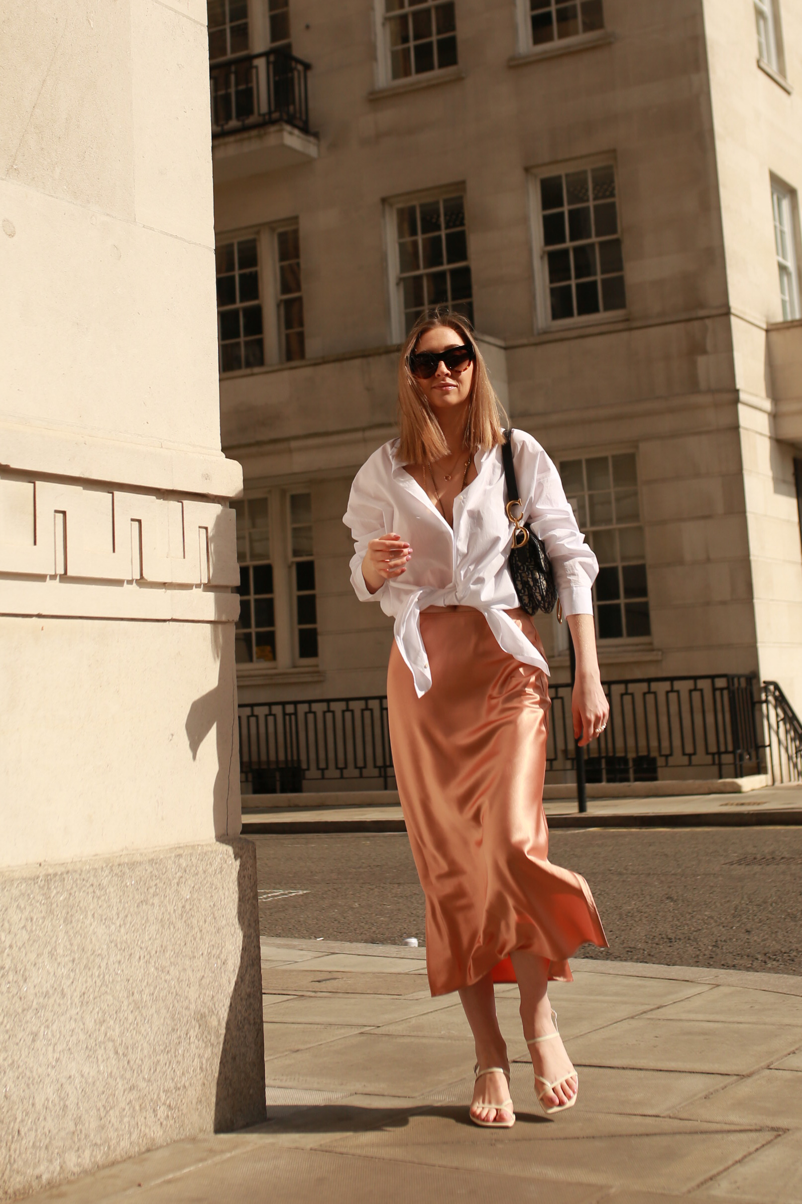 Silk Skirt in champagne colour with oversized white shirt tied into knot in front. Carrying Dior Oblique Saddle bag.
