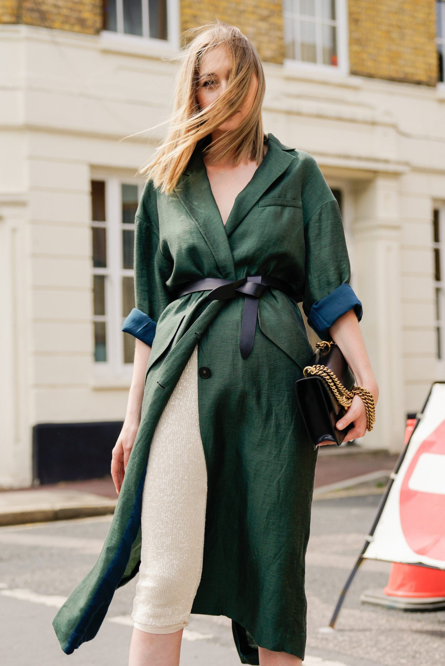 Lady in Zara green coat walking down the street.